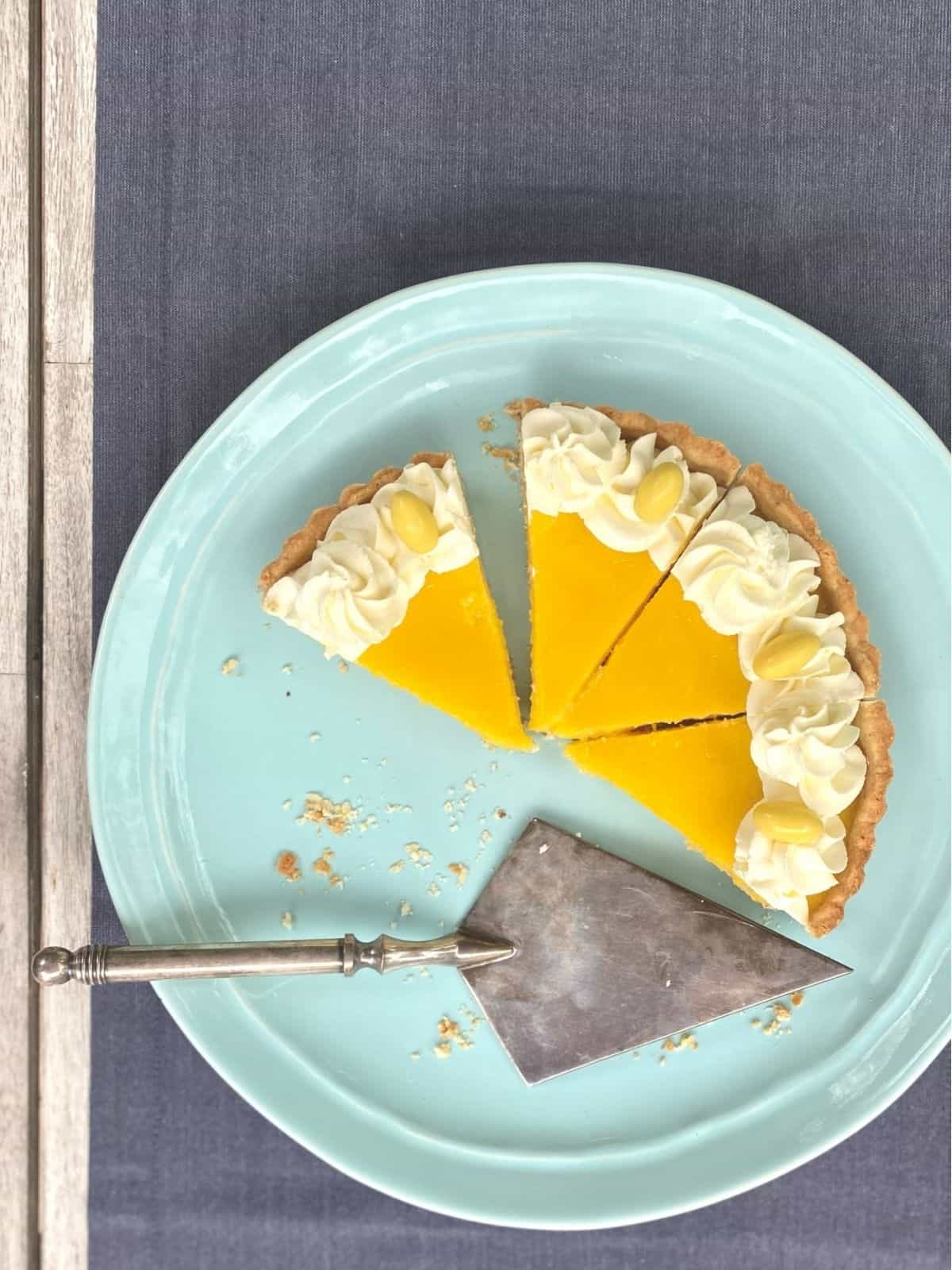 4 slices of lemon tart with whipped cream on blue plate