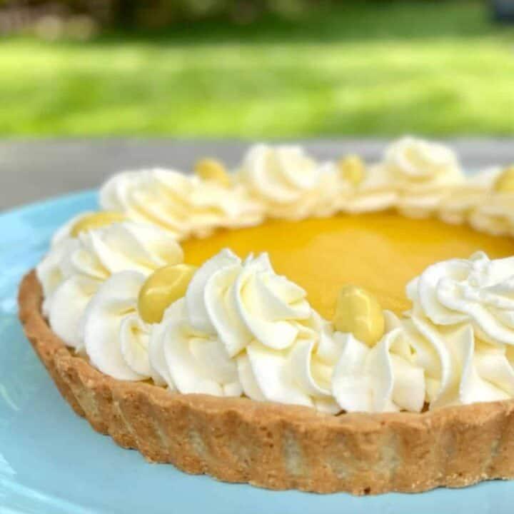 lemon tart with almond crust on blue plate