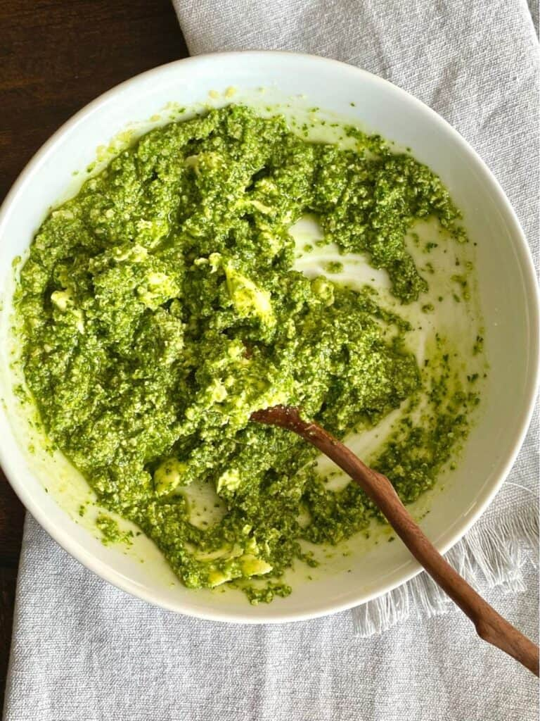 white bowl filled with pesto with wooden spoon