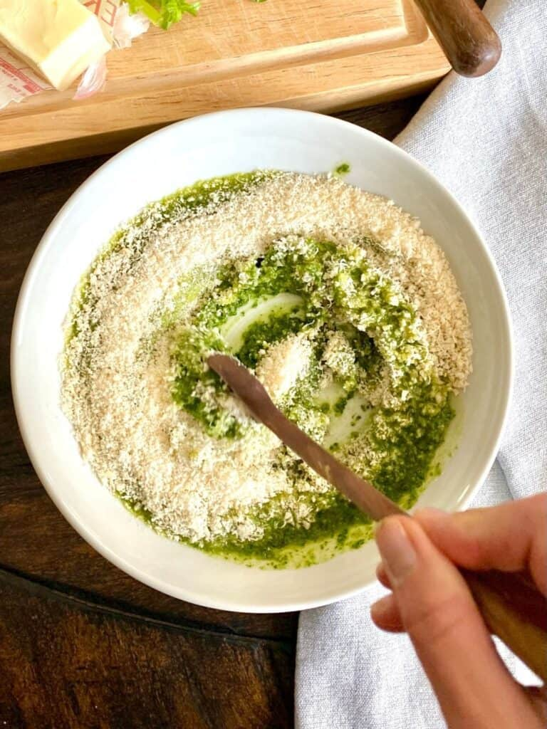 mixing cheese into pesto by hand