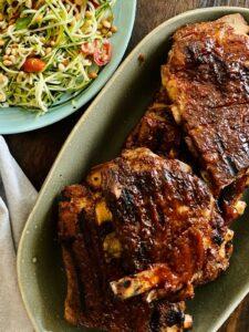platter of bbq ribs next to bowl of zucchini salad