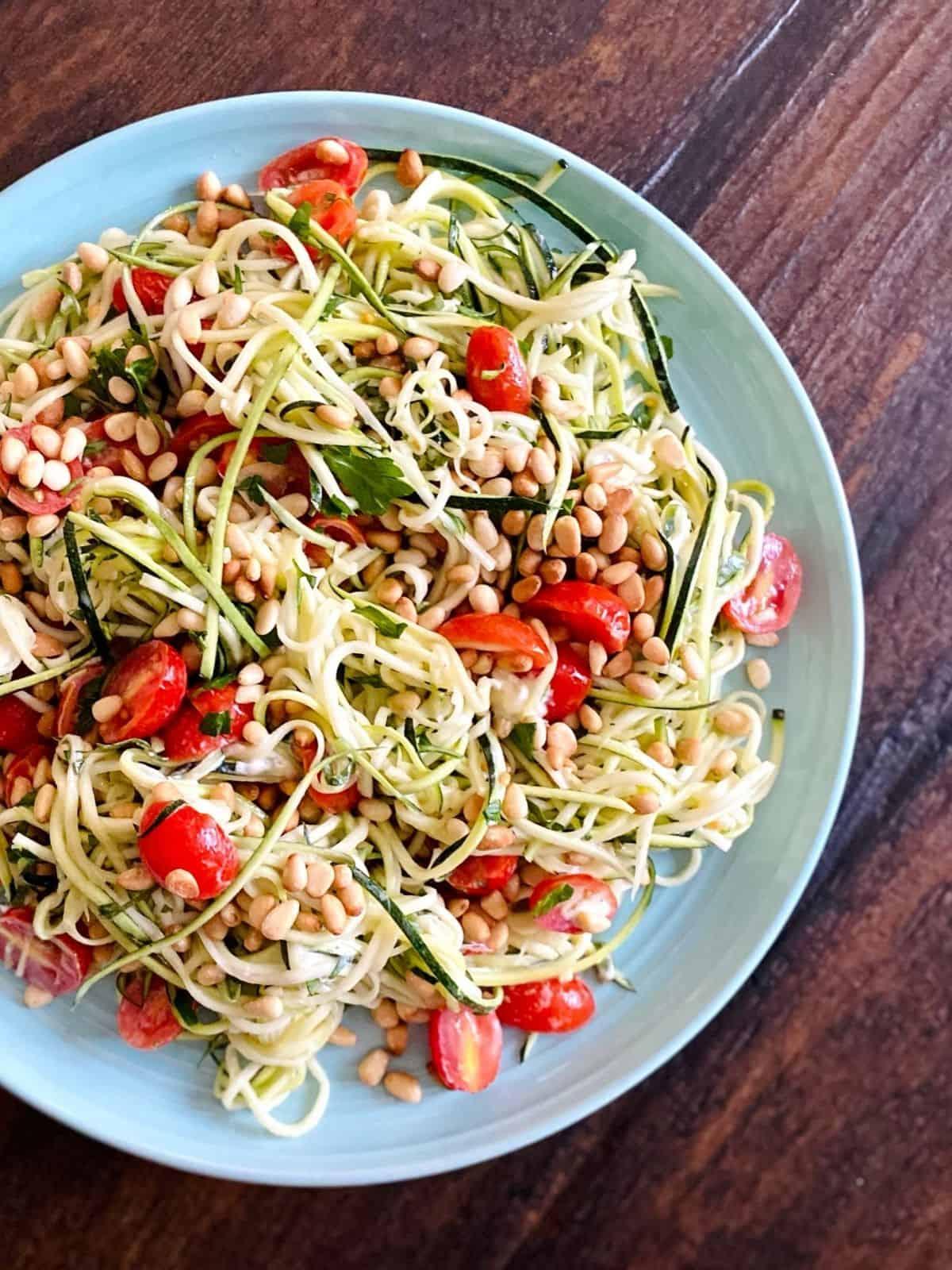 zucchini, tomato, pine nut salad in blue bowl