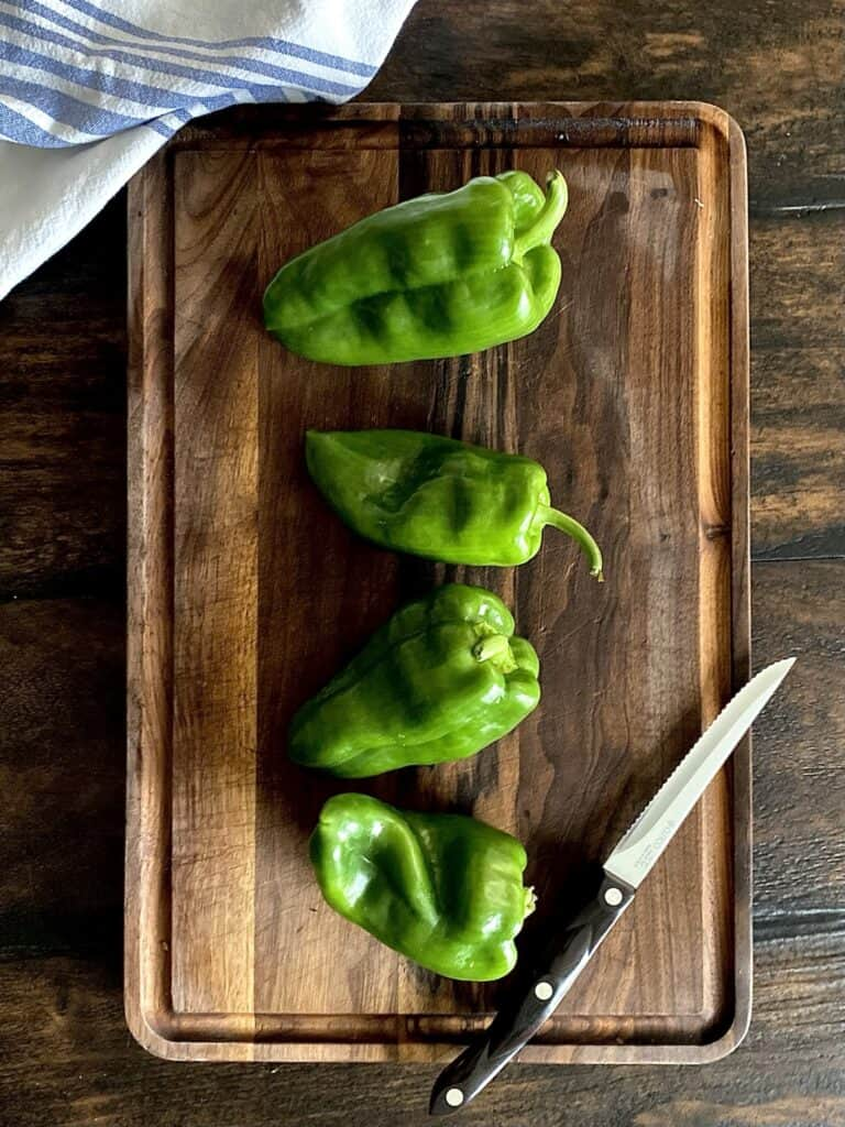 4 poblano peppers on a wood board with knife