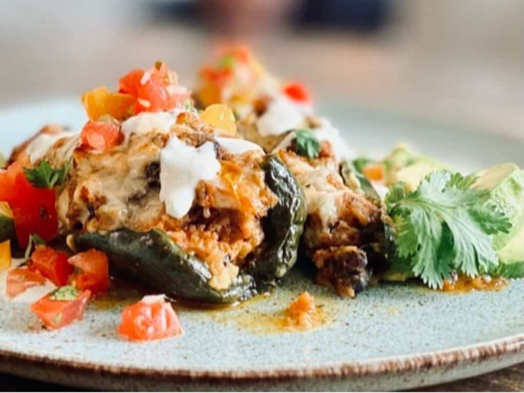 close up of stuffed poblano pepper on blue plate