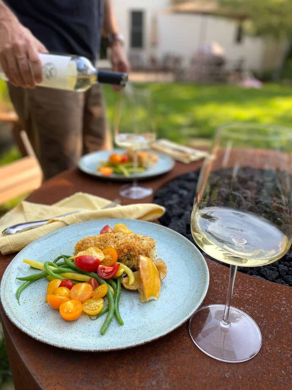 plated lemon basil rockfish with green beans and tomatoes next tp glass of wine