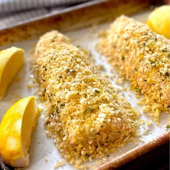 close up lemon basil rockfish on baking sheet with lemon wedges