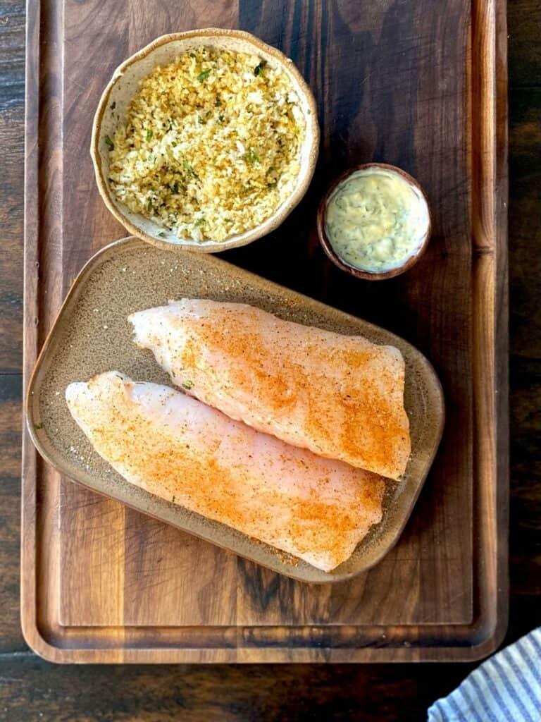 seasoned rockfish on wood board next to herb mayo and seasoned panko