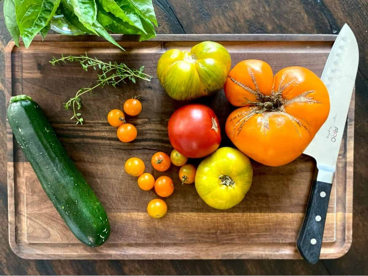 zucchini, tomatoes and herbs on wood board with knife