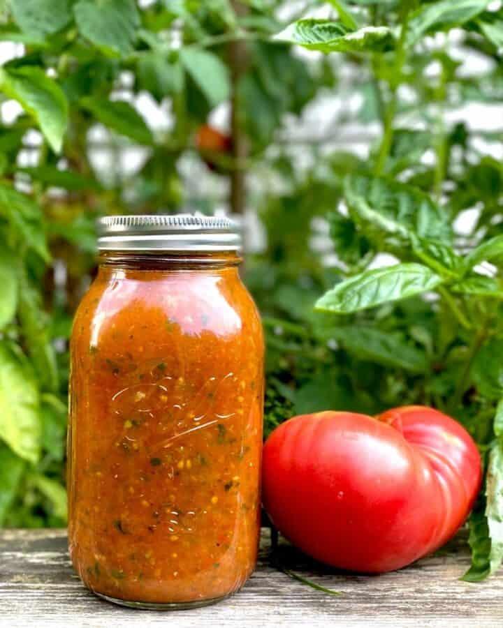 jar of roasted tomato sauce next to fresh tomato