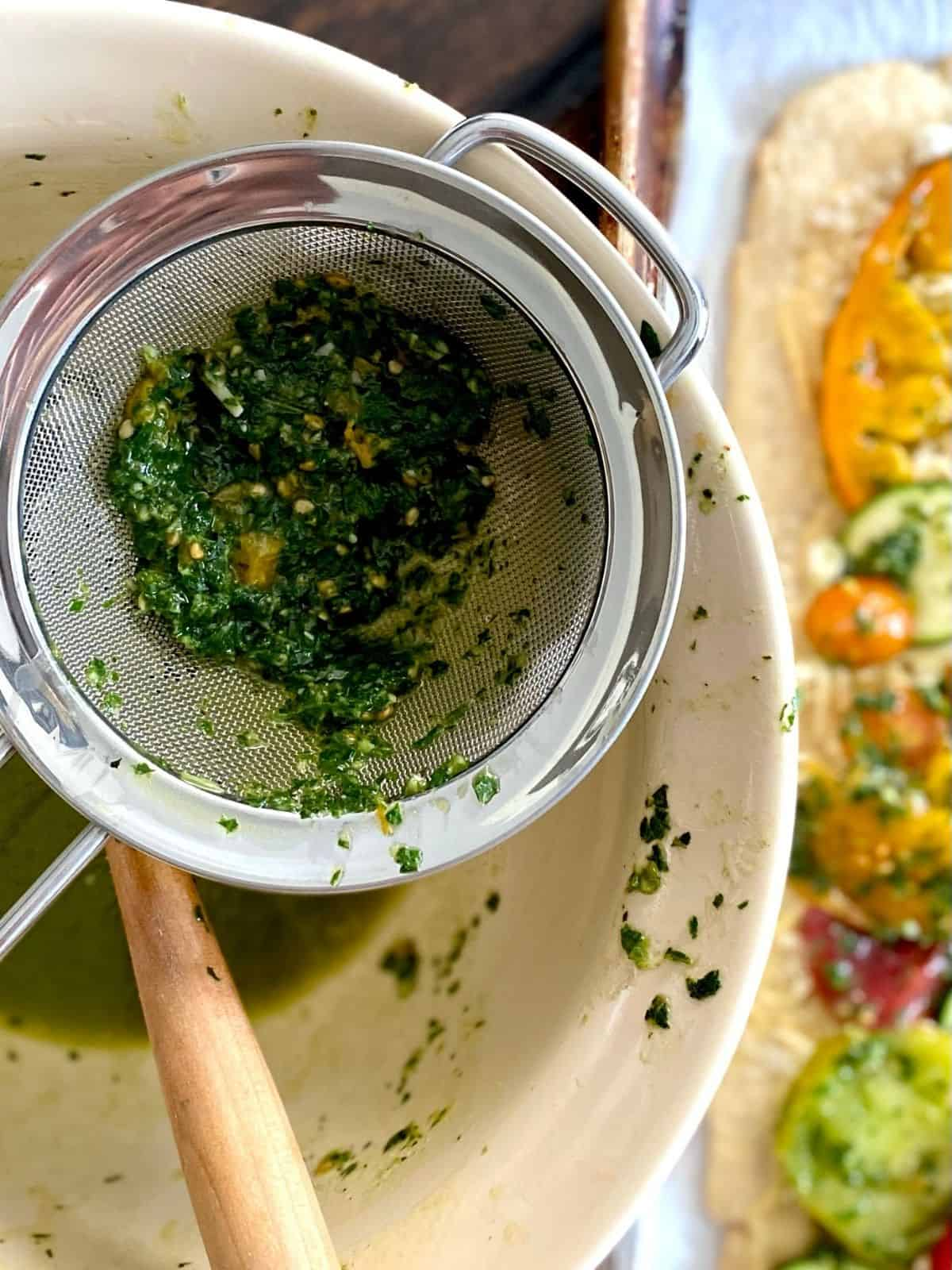 straining solids from herb mixture
