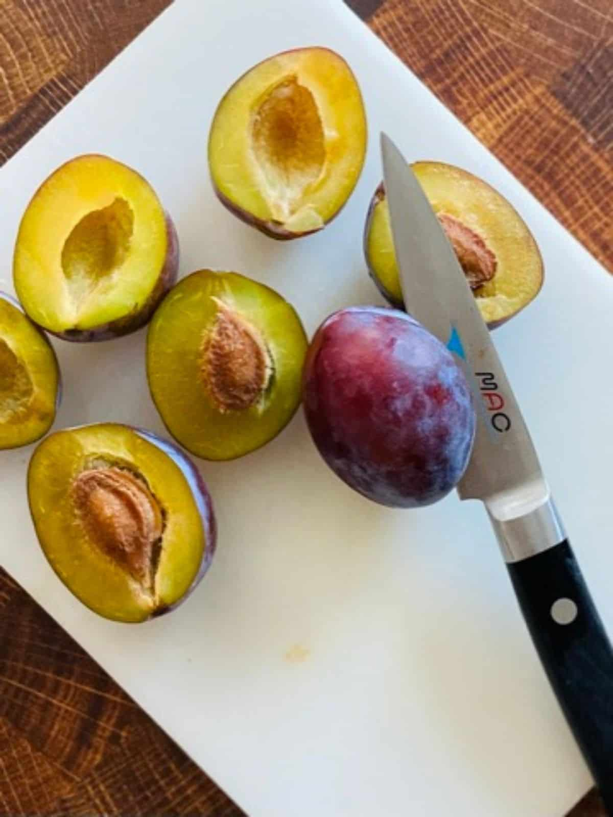 halved plums and knife