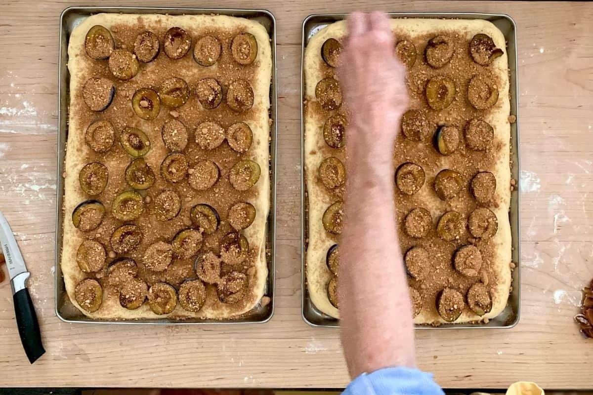 sprinkling crumbs on plum kuchen
